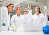Chemistry students looking at a liquid — Stock Photo