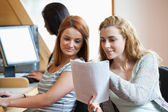 Happy student showing her notes to her classmate — Stock Photo
