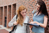 Student showing something to her classmate — Stock Photo