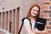 Smiling student holding her binder — Stock Photo
