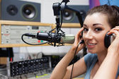Young radio host putting her headphones on — Stock Photo