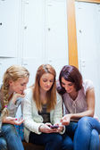 Portrait of a student showing a text message to her friends — Stock Photo