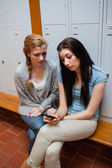 Portrait of a sad student showing a text message to her friend — Stock Photo