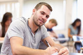 Smiling young adult writing — Stock Photo