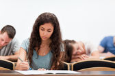 Students writing while their classmate is sleeping — Stock Photo