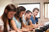 Students listening a lecturer with the camera focus on the foreg — Stock Photo