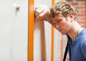 Close up of a lonely student leaning on a locker — Stock Photo