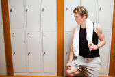 Handsome young sports student leaning on a locker — Stock Photo