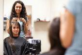 Femme peignant le cheveux d'un client — Photo