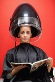 Portrait of a cute woman under a hairdressing machine — Stock Photo