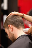 Portrait of a male young student having a haircut — Stock Photo