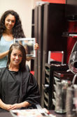 Portrait of a hairdresser showing to her customer her new haircu — Stock Photo