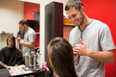 Smiling male hairdresser cutting hair — Stock fotografie