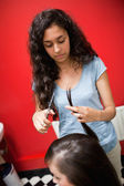 Portrait of a young female hairdresser cutting hair — Stock Photo