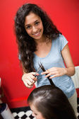 Portrait of a smiling female hairdresser cutting hair — Stock Photo