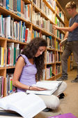 Portrait of a student reading a book while her classmate is choo — Stock Photo