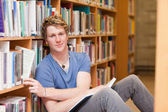 Handsome student picking a book — Stock Photo