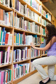 Portrait of a female student choosing a book — Stock Photo