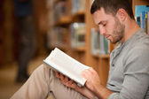 Serious male student reading a book — Stock Photo