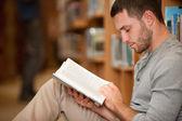 Ernsthaften männlichen studenten, die ein buch zu lesen — Stockfoto