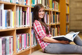 Smiling young female student holding a book — Stock Photo