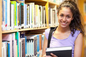 Smiling female student posing with a book — Stock Photo