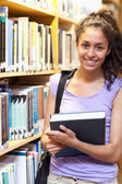 Portrait of a smiling female student posing with a book — Stock Photo