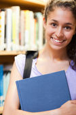 Portrait of a happy female student holding a book — Stock Photo