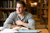 Smiling male student working — Stockfoto