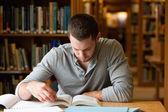 Estudante do sexo masculino pesquisando com um livro — Foto Stock