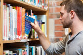 Male student picking a book — Stock Photo