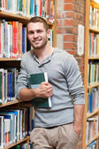 Portrait of a smiling male student holding a book — Stock Photo