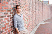 Male student leaning on a wall — Stock Photo