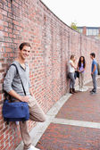 Portrait of a male student leaning on a wall while his friends are talking — Stock Photo