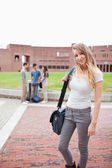 Portrait of a blond-haired student posing while her friends are talking — Stock Photo