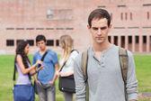 Estudante solitário posando enquanto seus colegas estão falando — Foto Stock