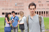 Solitario estudiante posando mientras sus compañeros están hablando — Foto de Stock