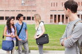 Student looking at his classmates talking — Stock Photo