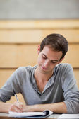 Portrait of a male student writing on a notepad — Stock Photo