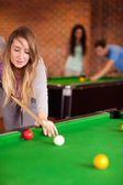 Portrait of a cute woman playing snooker — Stock Photo