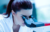Young scientist using a microscope — Stock Photo