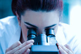 Young scientist looking through a microscope — Stock Photo