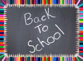 Back to school written on a blackboard framed with colored pencil — Stock Photo
