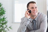 Businessman getting a pleasant call on his mobilephone — Stock Photo