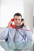 Businessman getting overextended by the telephone — Stock Photo
