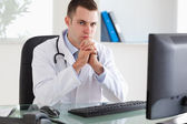 Doctor sitting behind his desk — Stock Photo