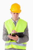 Portrait of a young builder taking notes — Stock Photo