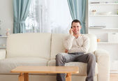 Man on the phone while sitting on his couch — Stok fotoğraf