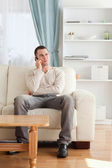 Portrait of a man on the phone while sitting on his sofa — Stock Photo