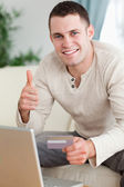 Portrait of a man purchasing online with the thumb up — Stock Photo